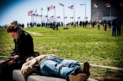 A couple relaxing under the shadow of the National Monument.
